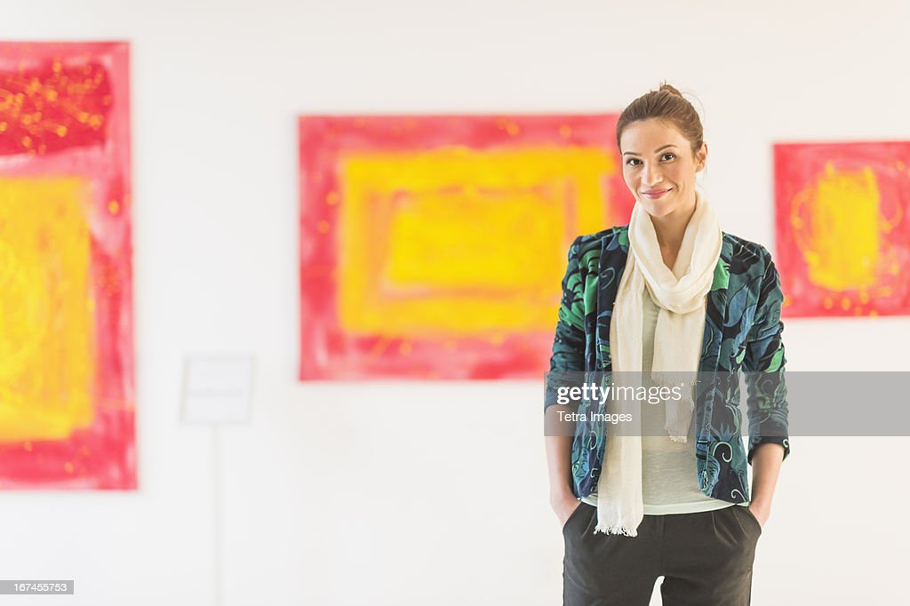 USA, New Jersey, Jersey City, Portrait of woman with paintings in museum : Stock Photo