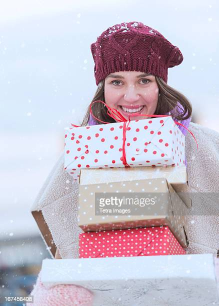 USA, New Jersey, Jersey City, Portrait of young woman carrying stack of Christmas presents