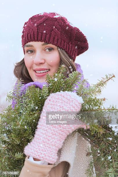 USA, New Jersey, Jersey City, Portrait of young woman wearing knit hat, gloves and scarf an carrying fir wreath