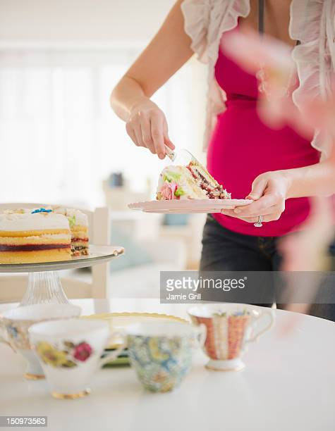 USA, New Jersey, Jersey City, Pregnant woman serving cake
