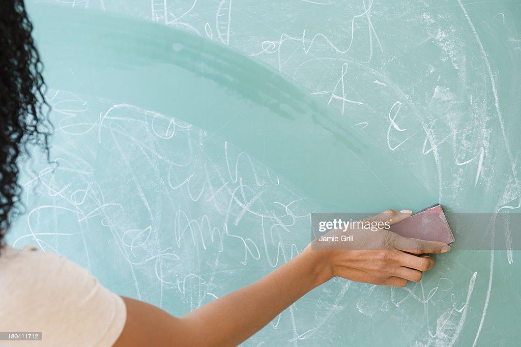 USA, New Jersey, Jersey City, Rear view of woman erasing blackboard : Stock Photo