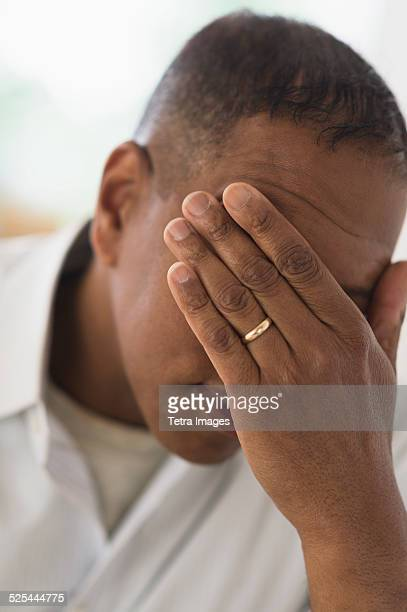 USA, New Jersey, Jersey City, Sad man covering face with hand