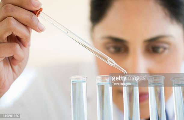 USA, New Jersey, Jersey City, Scientist pipetting liquid into test tubes
