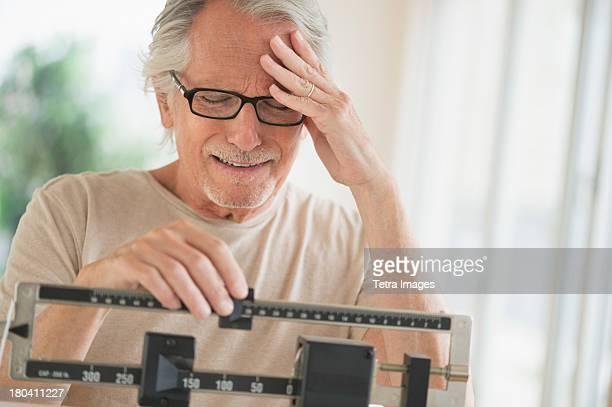 USA, New Jersey, Jersey City, Senior man on weight scale