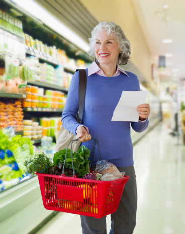 USA, New Jersey, Jersey City, Senior woman carrying shopping basket in supermarket - gettyimageskorea