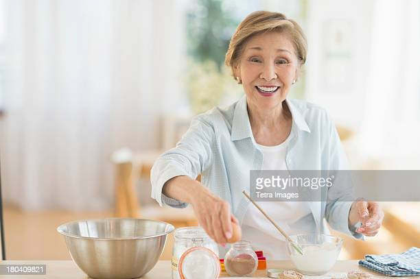USA, New Jersey, Jersey City, Senior woman cooking in kitchen