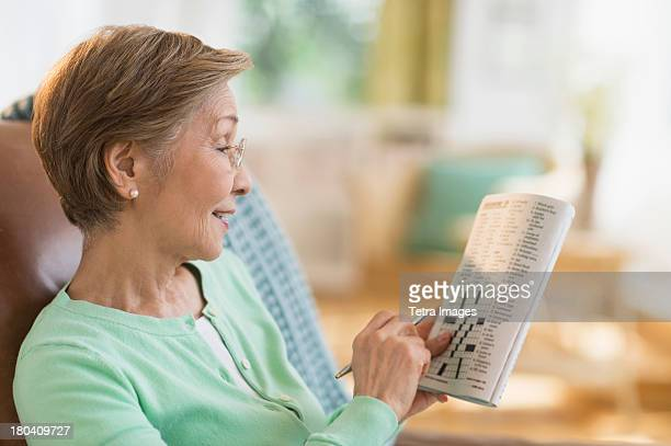 USA, New Jersey, Jersey City, Senior woman doing crossword puzzle