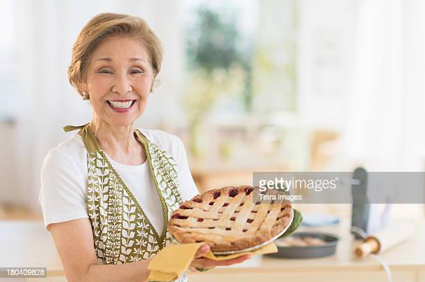 USA, New Jersey, Jersey City, Senior woman holding freshly baked cake