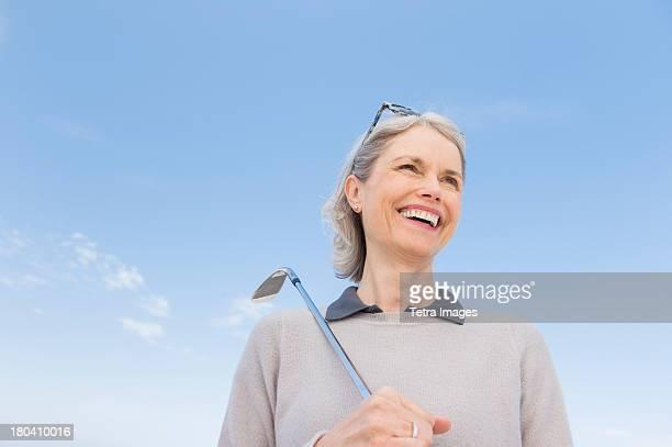 USA, New Jersey, Jersey City, Senior woman holding golf club