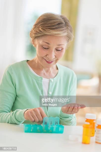 USA, New Jersey, Jersey City, Senior woman organizing medicine in box