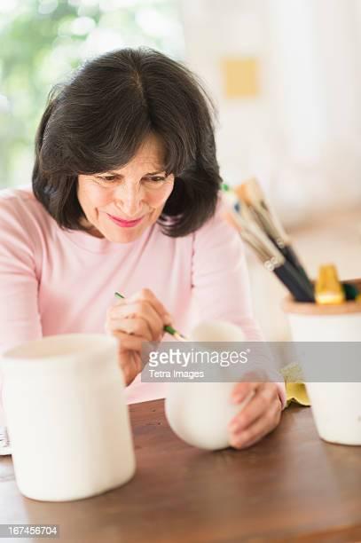 USA, New Jersey, Jersey City, Senior woman painting handmade pottery