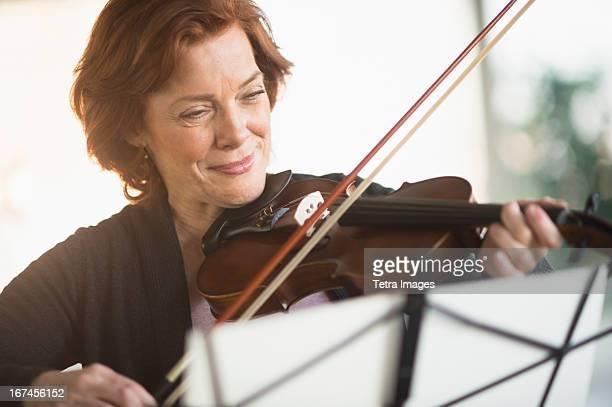 USA, New Jersey, Jersey City, Senior woman playing violin