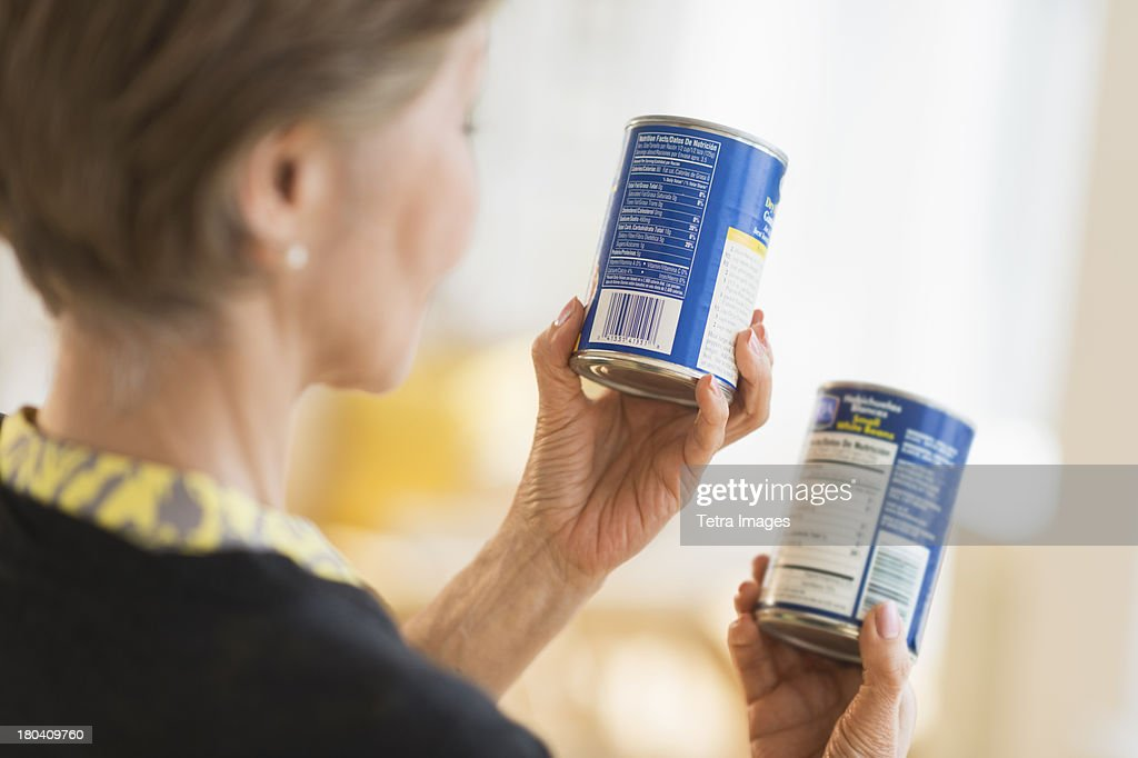 USA, New Jersey, Jersey City, Senior woman reading labels on canned food : Stock Photo