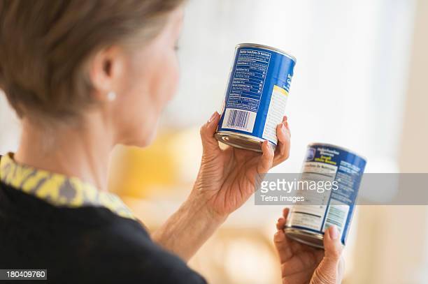 usa, new jersey, jersey city, senior woman reading labels on canned food - canned food stock pictures, royalty-free photos & images
