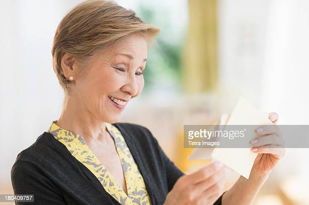 USA, New Jersey, Jersey City, Senior woman reading note