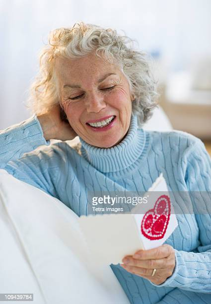USA, New Jersey, Jersey City, Senior woman reading Valentines card in living room