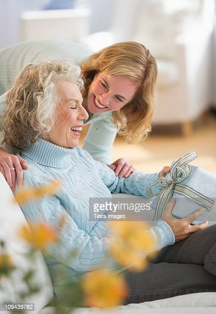 USA, New Jersey, Jersey City, Senior woman receiving present from daughter on sofa