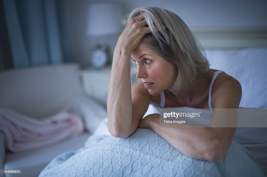 USA, New Jersey, Jersey City, Senior woman sitting in bed and suffering from insomnia : Stock Photo