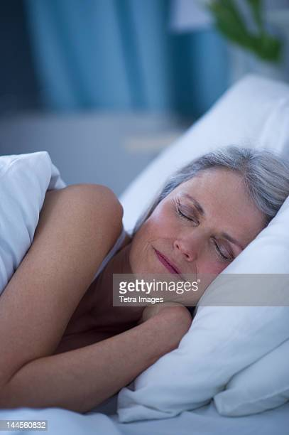 usa, new jersey, jersey city, senior woman sleeping in bed - lying on side stock pictures, royalty-free photos & images