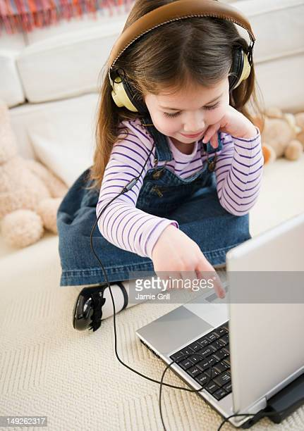 usa, new jersey, jersey city, small girl (4-5 years) listening to music from laptop - 4 5 years stock pictures, royalty-free photos & images