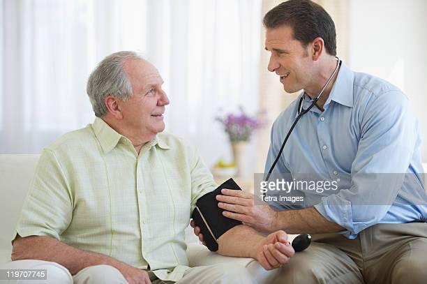 USA, New Jersey, Jersey City, Smiling man taking senior man's blood pressure