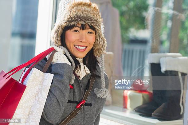 usa, new jersey, jersey city, smiling woman during christmas shopping - one mid adult woman only stock pictures, royalty-free photos & images