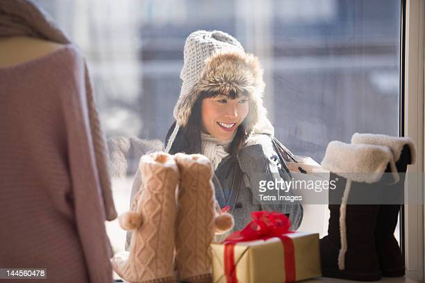USA, New Jersey, Jersey City, Smiling woman looking at shop display during Christmas shopping