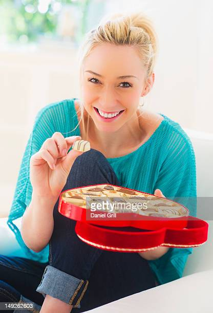 USA, New Jersey, Jersey City, Smiling young woman eating chocolates