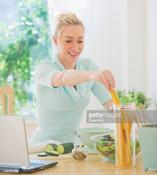 USA, New Jersey, Jersey City, Smiling young woman preparing food in kitchen