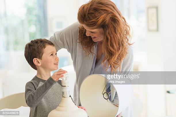 USA, New Jersey, Jersey City, Son (6-7) and mother changing lightbulb in table lamp