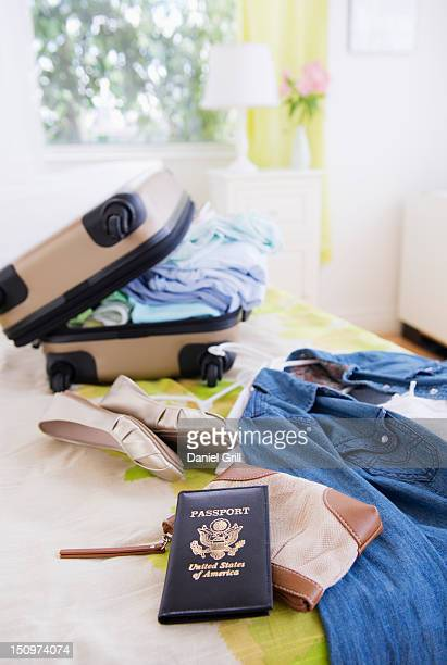 USA, New Jersey, Jersey City, Suitcase and passport on bed during packing