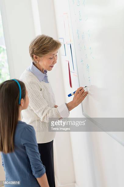USA, New Jersey, Jersey City, Teacher and schoolgirl (8-9) writing at whiteboard
