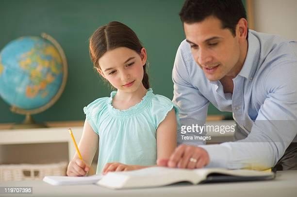 USA, New Jersey, Jersey City, teacher helping schoolgirl (8-9)