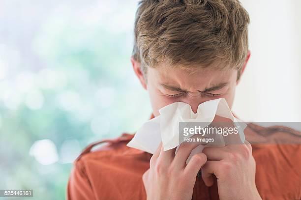 USA, New Jersey, Jersey City, Teenage boy (16-17) blowing nose