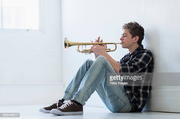 USA, New Jersey, Jersey City, Teenage boy (16-17) playing trumpet in hallway