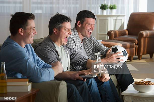 USA, New Jersey, Jersey City, three men watching television
