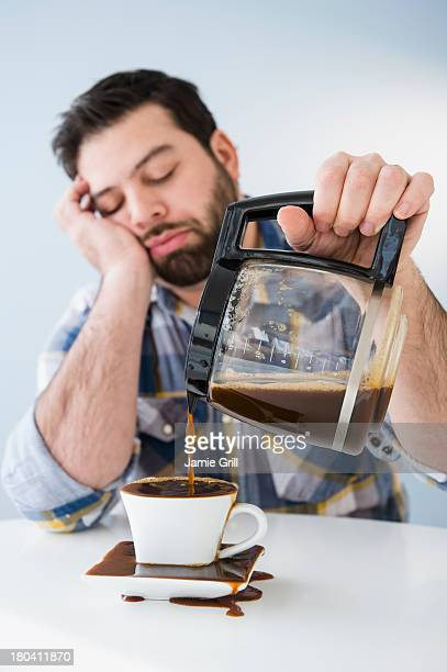 usa, new jersey, jersey city, tired, sleepy man spilling coffee on table - overflowing stock pictures, royalty-free photos & images