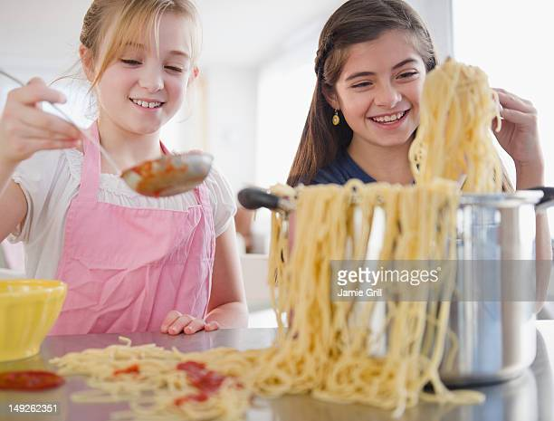 USA, New Jersey, Jersey City, Two girls cooking pasta