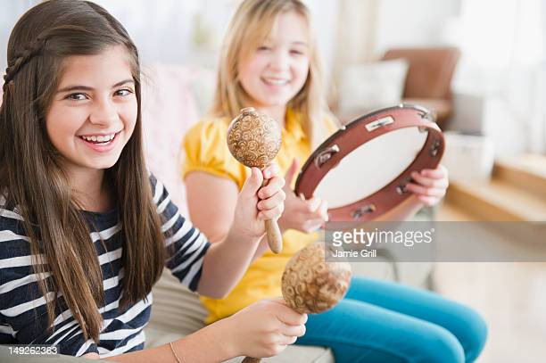 usa, new jersey, jersey city, two girls playing music on instruments - tambourine stock pictures, royalty-free photos & images