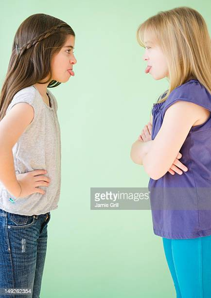 USA, New Jersey, Jersey City, Two girls standing face to face and sticking out tongues