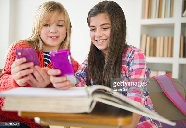 USA, New Jersey, Jersey City, Two girls using mobile phones