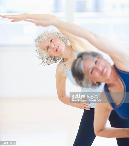 USA, New Jersey, Jersey City, Two senior women stretching