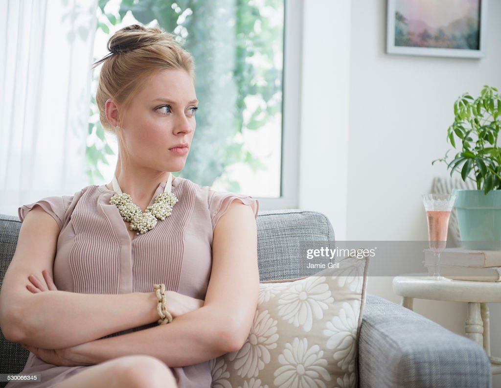 USA, New Jersey, Jersey City, Upset young woman sitting on sofa : Stock Photo