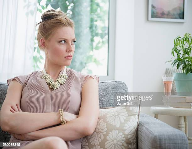 USA, New Jersey, Jersey City, Upset young woman sitting on sofa