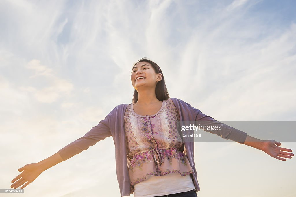 USA, New Jersey, Jersey City, Upward view of teenage girl ( 16-17 years) standing with arms raised : Stock Photo