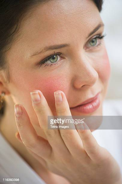 USA, New Jersey, Jersey City, woman applying cosmetics on face