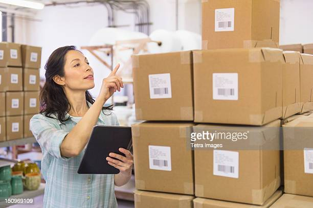 USA, New Jersey, Jersey City, Woman counting boxes in warehouse