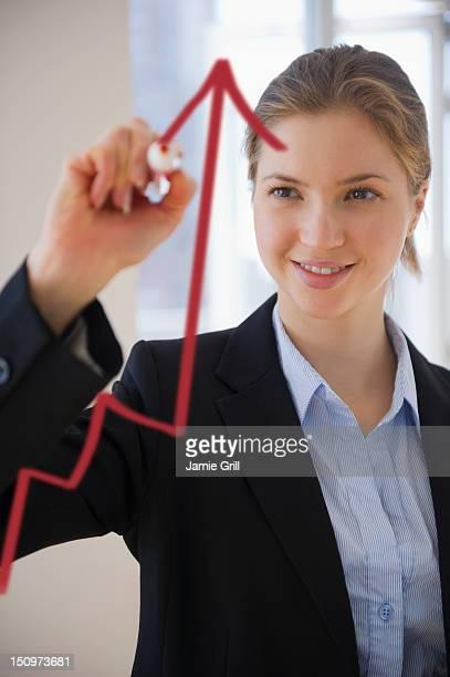 USA, New Jersey, Jersey City, Woman drawing graph on glass