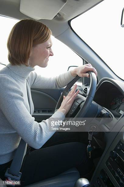 USA, New Jersey, Jersey City, woman driving and honking car horn