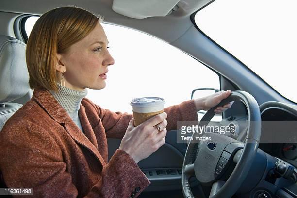 USA, New Jersey, Jersey City, woman driving car and drinking coffee